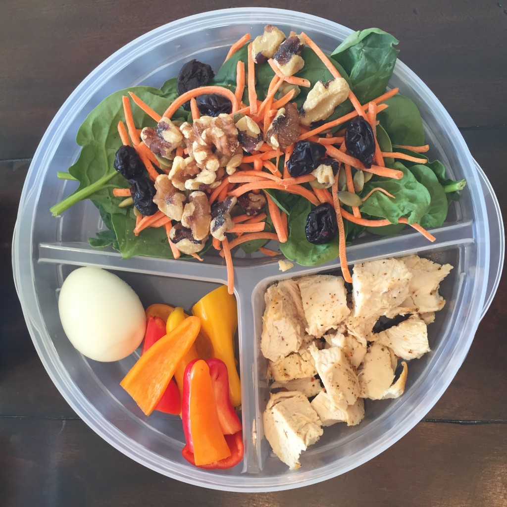Fresh spinach, shredded carrots, dried cherries, pumpkin seeds, walnuts, chicken breast a boiled egg and fresh bell peppers